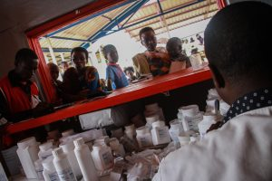 Patients queue for medicine at the Pharmacy in Save the Children's Health Centre in Mahama Refugee Camp Rwanda