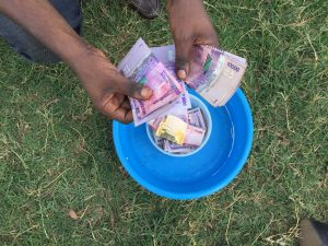 A member of Tumaini saving group counting money that members have saved