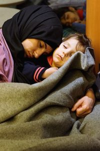 Woman and child sleeping after arriving on Lesvos by boat. © Karim Ani