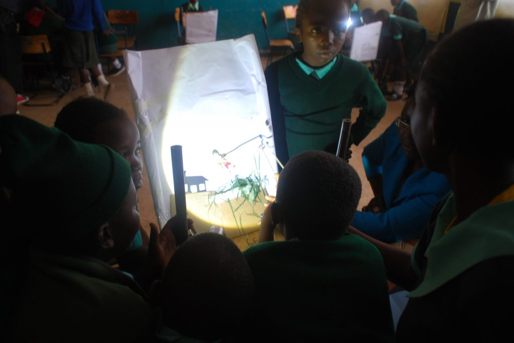 A group of children rehearsing a very moving shadow show story the created about a life saved by handwashing with soap