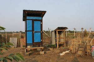 The popular new Tiger Worm Toilet (left) in Mingan IDP village, next to the family's previous toilet (right). Credit: Lucy Polson/Oxfam