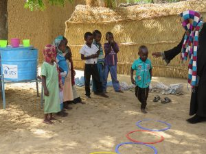 A Little Ripples teacher leading outdoor play in refugee camp Goz Amer. Photo Credit: iACT